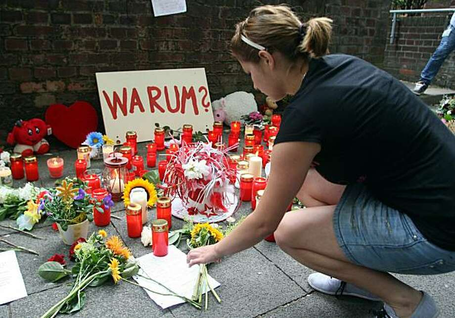 DUISBURG, GERMANY - JULY 25:  A mournour expresses her condolence on the day after a stampede at Germany's famous Love Parade festival killed at least 18 revellers, on July 25, 2010 in Duisburg, Germany. Hundreds more were injured as a mass panic spread amongst thousands of people who were stuck in a tunnel which acted as the only entrance into the festival grounds. Photo: Getty Images