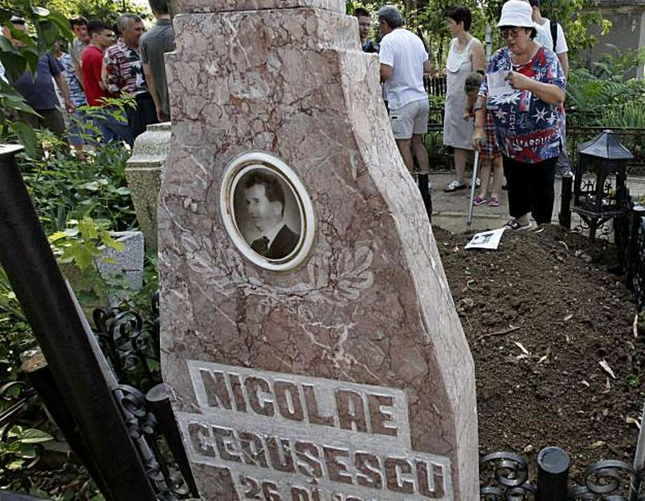 Media and members of the public gather around  the freshly dug up grave of late communist dictator Nicolaie Ceausescu at the Ghencea cemetery in Bucharest, Romania, Wednesday, July 21, 2010.  Taking the country by surprise, forensic scientists on Wednesday July 21, 2010, exhumed what are believed to be the bodies of Romanian dictator Nicolae Ceausescu and his wife Elena at the request of their children. Photo: AP