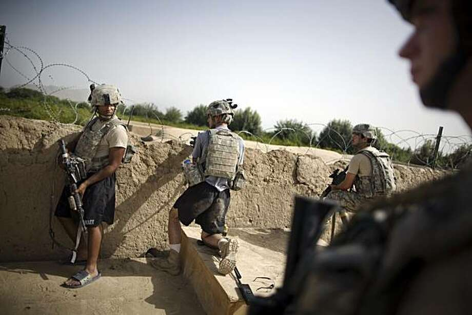 U.S. Army soldiers of the 1-320th Alpha Battery, 2nd Brigade of the 101st Airborne Division, look towards insurgent positions after a firefight at COP Nolen, in the volatile Arghandab Valley in Kandahar, Afghanistan, Saturday, July 24, 2010. Photo: Rodrigo Abd, AP