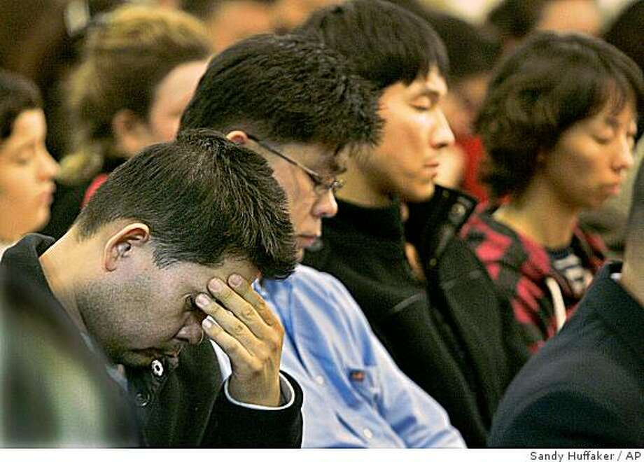 Dong Yun Yooh, left, weeps Wednesday, Dec. 10, 2008 at the Korean United Methodist Church during a memorial service for his family, wife Young Mi Yoon , daughters Grace Yoon and Rachel Yoon,  and mother-in-law Suk Im Kim, who were killed on Monday when an F/A-18D Hornet crashed into their home in San Diego.  (AP Photo/Sandy Huffaker) Photo: Sandy Huffaker, AP