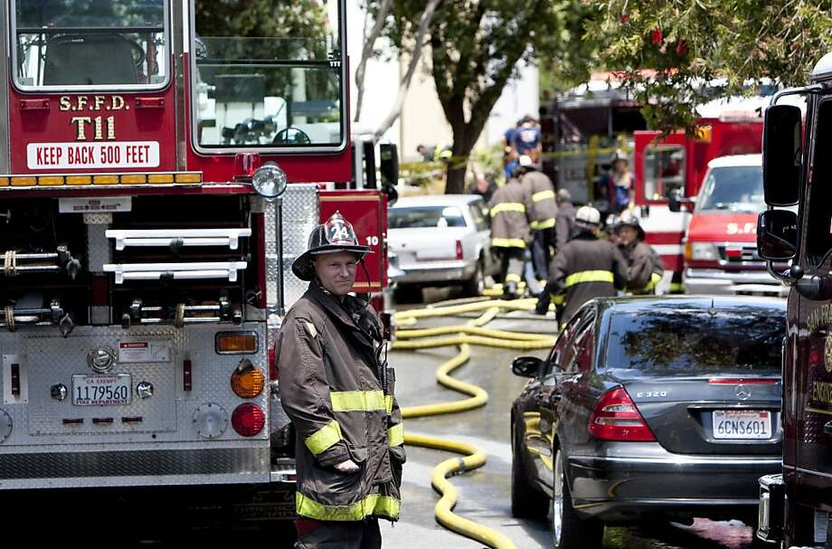 A firefighter stands on the 100 block of Berkeley Way in the Diamond Heights neighborhood where a fire Thursday morning left two firefighters battling the blaze seriously burned and a third with minor injuries in San Francisco, Calif., on Thursday, June 2, 2011. Photo: Laura Morton, Special To The Chronicle
