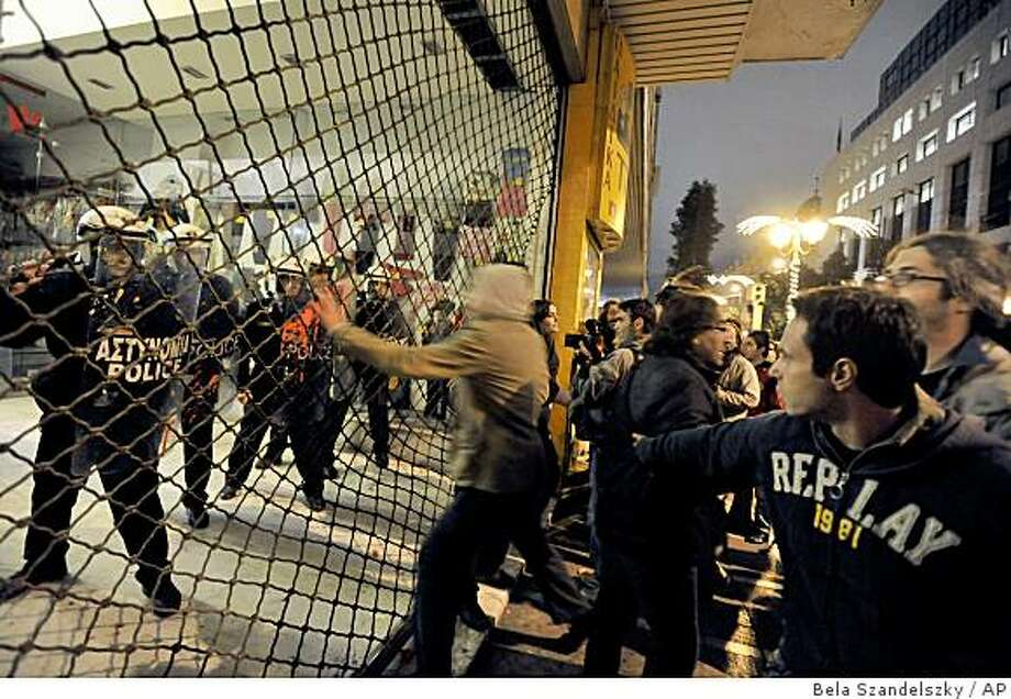 Youths shout at riot police behind shutters at a building of Greece's Interior Ministry during clashes on the sidelines of a demonstration in central Athens, Greece, on Thursday, Dec. 11, 2008. Sporadic violence persisted Thursday after Greece's worst rioting in decades, with students attacking police stations and vowing to stay on the streets as the protests broadened from rage over the police killing of a teenager to a wider rebellion against economic hardship. (AP Photo/Bela Szandelszky) Photo: Bela Szandelszky, AP