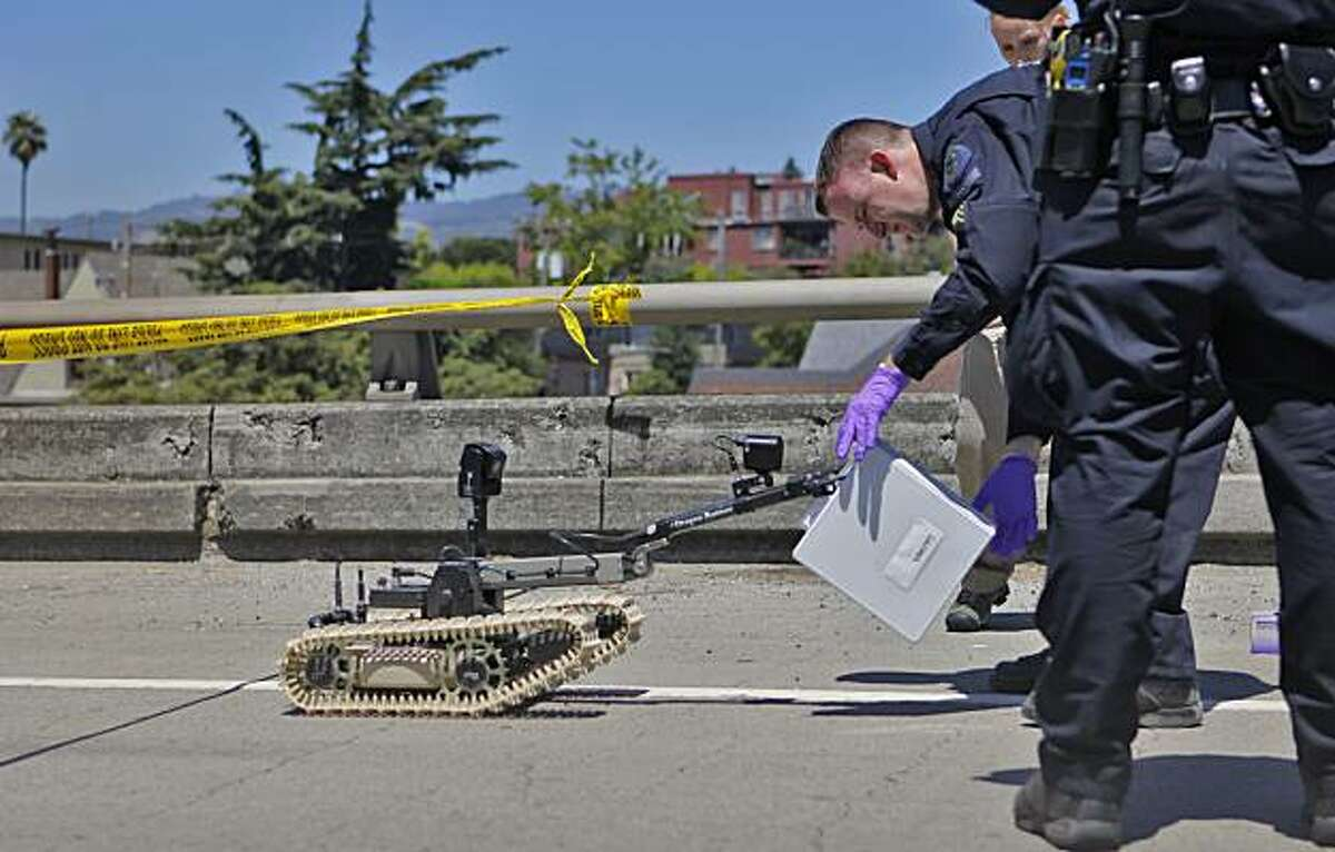 Alameda County Bomb Squad Sgt. Ray Kelly takes evidence the squad's robot retrieved from the shootout suspect's truck Sunday in Oakland.