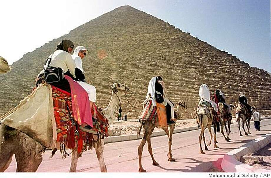 TRAVEL EGYPT CAIRO -- Tourists ride camels in front of the Great Pyramid, built 4,500 years ago by Khufu, a ruler also known as Cheops on Friday Sept. 13, 2002. Photo: Mohammad Al Sehety, AP