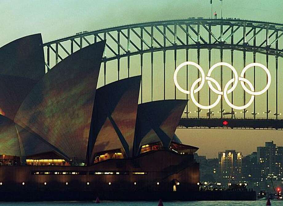 The famous Sydney Harbour Bridge with the Olympic rings and the Opera House with the Earth lighting projection are lit up in Sydney, Thursday, September 14, 2000. The opening of the 2000 Summer Games will start Friday in Sydney. Photo: Rob Griffith, AP