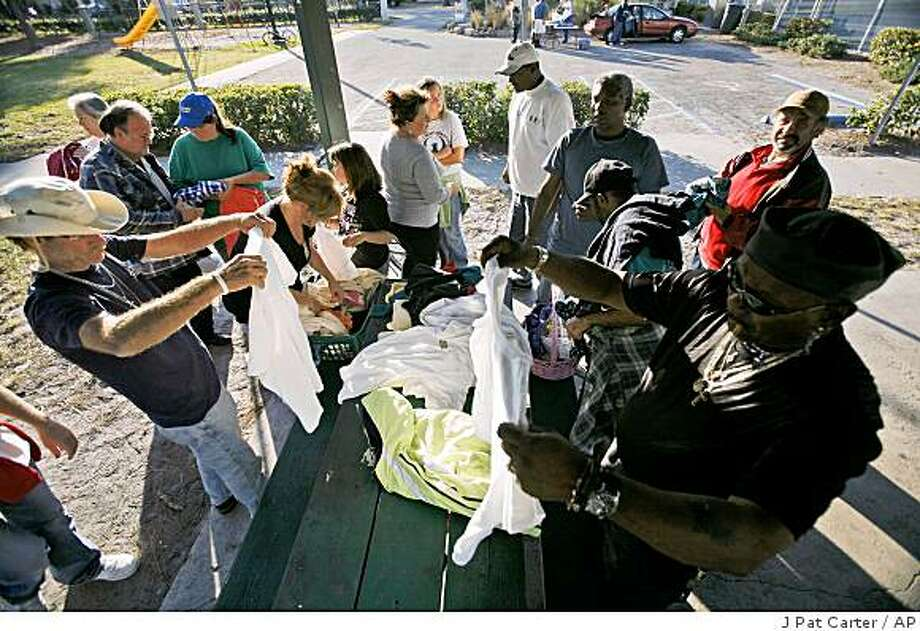 Sharie Zipperer, center, gives out blankets and clothing to the homeless in Lions Park in Fort Myers, Fla. Friday, Dec. 5, 2008. (AP Photo/J Pat Carter) Photo: J Pat Carter, AP