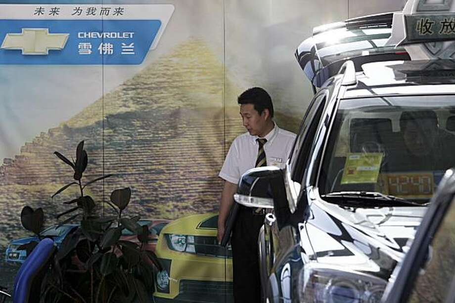 A salesman at a General Motors Co. Chevrolet shows a Captiva sport utility vehicle to a customer in Beijing, China, on Friday, July 2, 2010. General Motors Co.'s first-half sales in China surpassed those in the U.S. for the first time as the world's fastest-growing major economy propelled global auto demand. Photographer: Nelson Ching/Bloomberg Photo: Nelson Ching, Bloomberg