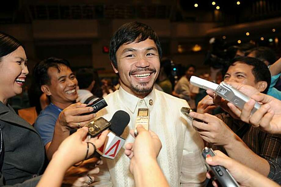 Philippine boxing hero and now congressman Manny Pacquiao speaks to members of the media on the sidelines of their orientation seminar at the House of Representatives in Manila on July 8, 2010.  A former president currently under investigation for corruption, a shoe-obsessed ex-first lady, and a world champion boxer were just a few of the colourful characters from Filippino politics who gathered in Manila July 8. Photo: Ted Aljibe, AFP/Getty Images
