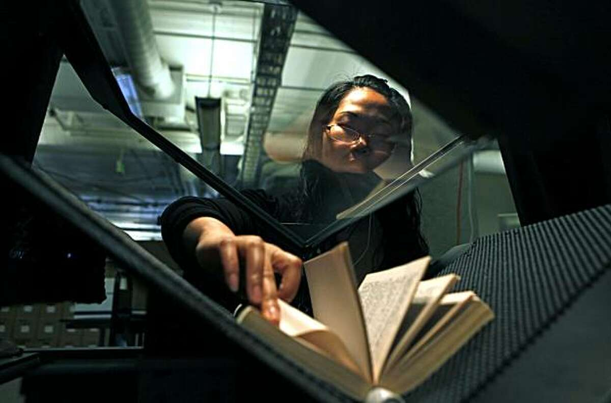 The Internet Archives employee Silken Wuang flips pages on a San Francisco library book that she is digitizing.