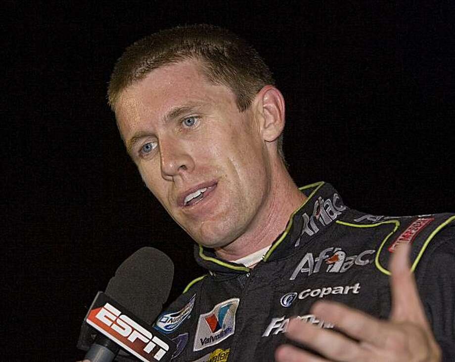 In this Saturday, July 17, 2010, photo, Carl Edwards is interviewed after winning the NASCAR Nationwide Series auto race in Madison, Ill. Edwards sees no reason why he shouldn't compete for the NASCAR Sprint Cup and the sport's second-tier title at the same time. NASCAR has considered changes to the Nationwide Series that could affect the participation of Cup drivers, who routinely dip down to take victories against smaller teams and less-experienced drivers. (AP Photo/Belleville News-Democrat, Tim Vizer Photo: Tim Vizer, AP