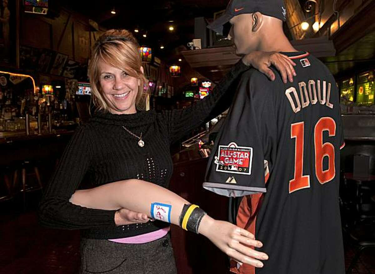 Darlene Sularski poses with the left arm of the mannequin from