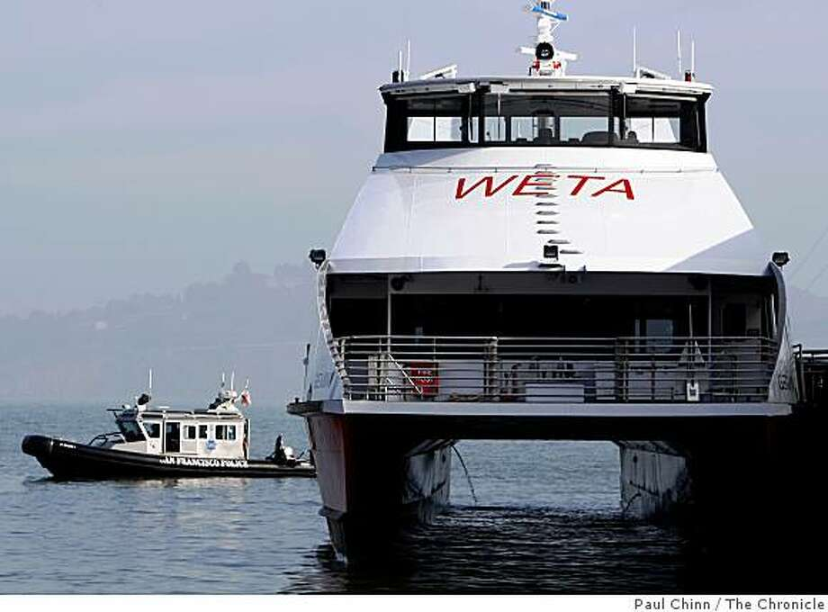 A San Francisco police boat patrols behind the ferry boat Gemini which was christened by officials with the Water Emergency Transportation Authority in San Francisco, Calif., on Friday, Dec. 12, 2008. Photo: Paul Chinn, The Chronicle