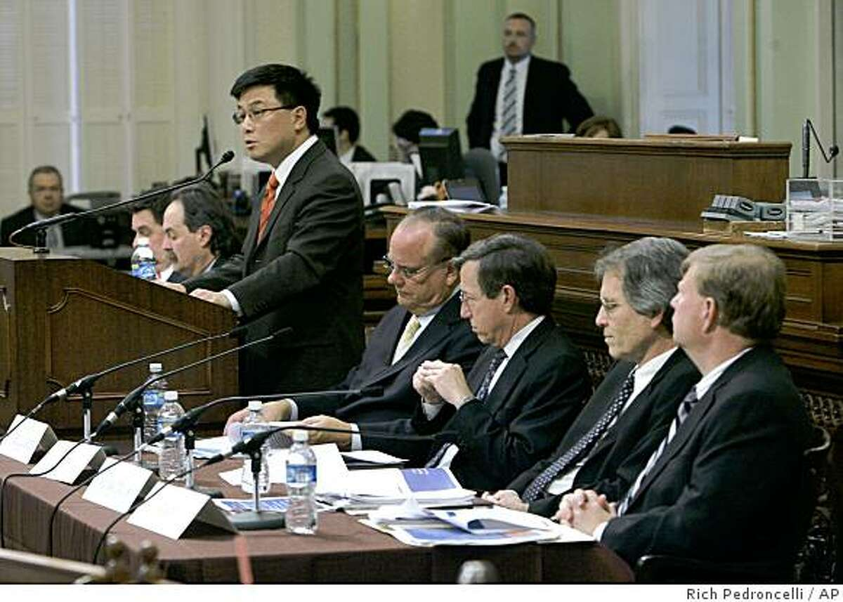 California State Controller John Chiang, standing, discusses the growing state budget deficit while appearing with a panel at a joint special session of the Legislature at the Capitol in Sacramento, Calif., Monday, Dec. 8, 2008. (AP Photo/Rich Pedroncelli)