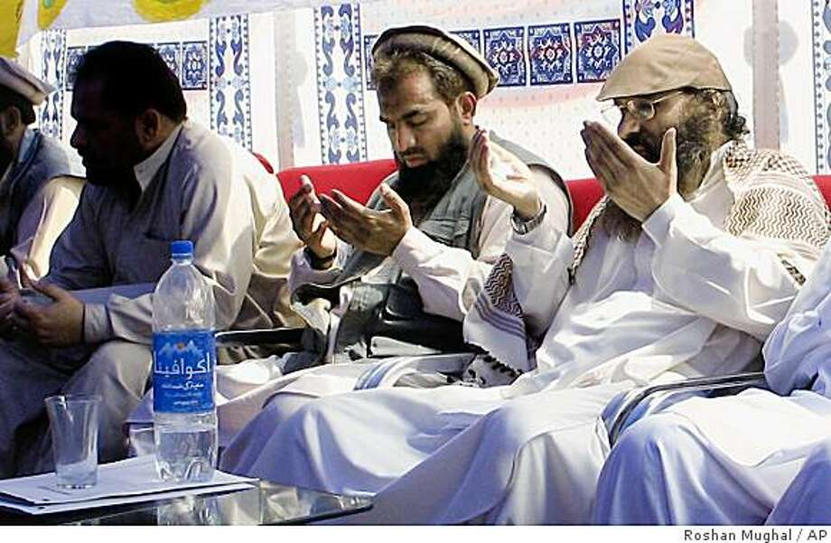 An alleged plotter of Mumbai attacks, Pakistani Zaki-ur-Rehman Lakhvi, center, prays with Syed Salahuddin, right, chief of Hezbul Mujahedeen, or United Jehad Council, at a rally on Saturday, June 28, 2008, in Muzaffarabad, capital of Pakistani Kashmir. Pakistan has detained Zarrar Shah, another alleged mastermind of the Mumbai terrorist attacks, Pakistani Prime Minister Yousuf Raza Gilani confirmed Wednesday, Dec. 10, 2008, apparently making good on pledges to pursue the perpetrators. (AP Photo/Roshan Mughal) Photo: Roshan Mughal, AP