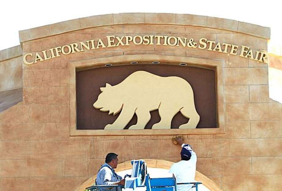 Workers clean an archway at Cal Expo, Monday, July, 12, 1010,  in preparation for Wednesday's opening of the State Fair in Sacramento, Calif. The fair is opening a month earlier then normal in hopes attracting more visitors before children return to school in August. Photo: Rich Pedroncelli, AP