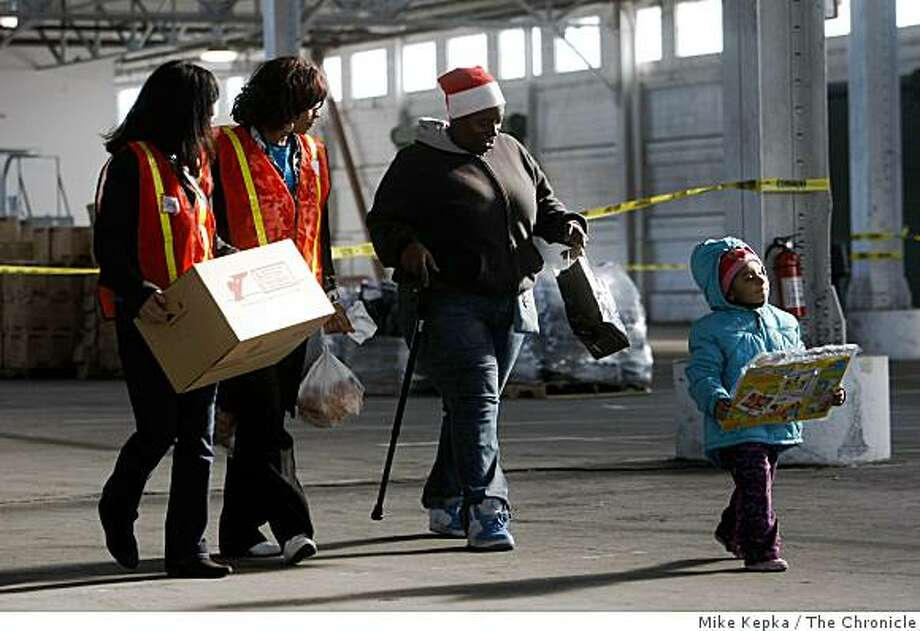 "Volunteers from PG&E, Corinne Chung (l) and Patrician Regan carry boxes of food for Yvon Green and her granddaughter Angelina Golson, 3, during ""The Miracle at Pier 48"" event in which ""Feed The Children, The Willie Brown Institute, The National Basketball Players Assoc. and other local partners join forces to distribute food and toys to 5,000 San Francisco families in need on Thursday, Dec. 11, 2008 in San Francisco, Calif. Photo: Mike Kepka, The Chronicle"