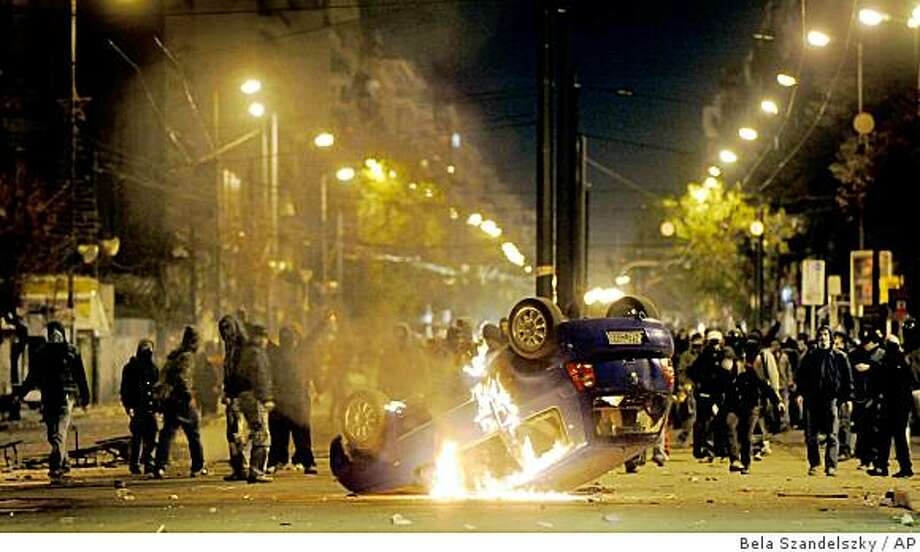 Greek rioters burn a car while clashing with police in Athens, Wednesday, Dec. 10, 2008. A fifth day of rioting erupted in the Greek capital on Wednesday, on a day with pitched battles between police and rioters. The troubles started following the fatal shooting of a 15-year-old boy by a police officer Saturday night. (AP Photo/Bela Szandelszky) Photo: Bela Szandelszky, AP