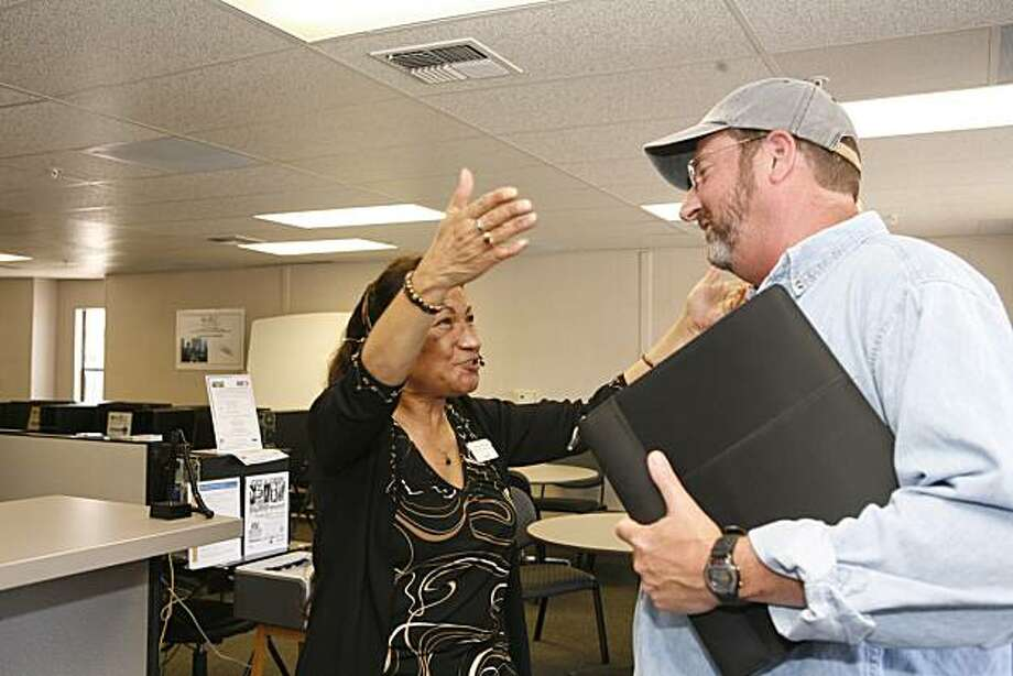 Customer service representative at the NUMMI re-employment center, Sylvia Rios, reacts when hearing of client Ray Simpson's (right) success in finding a job through the center on Monday July 12, 2010 in Fremont, Calif.  The NUMMI re-employment center is a a one-stop career center specifically for displaced NUMMI workers. Photo: Jasna Hodzic, The Chronicle