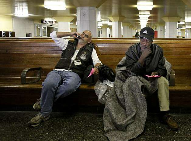Homeless counselor Jason Albertson (left) made a phone call to get Ed Jones (right) into a shelter after he was found napping at the Transbay Terminal Thursday July 15, 2010. San Francisco, Calif. city health and homeless-aid counselors are trying to help and relocate dozens of homeless people who live in the Transbay Terminal and the immediate area.  The terminal will be shut down August 7, 2010 and will be demolished for a new transit hub. Photo: Brant Ward, The Chronicle