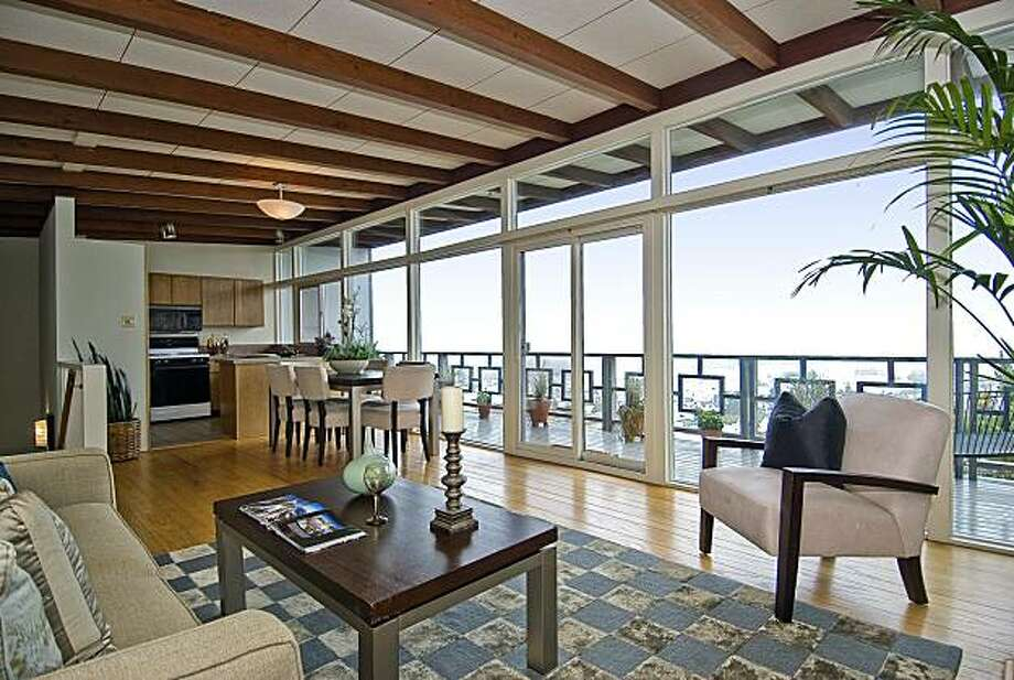The home's great room includes a living area, dining area and kitchen. It also features floor-to-ceiling windows that open to a rear deck. Photo: OpenHomesPhotography.com
