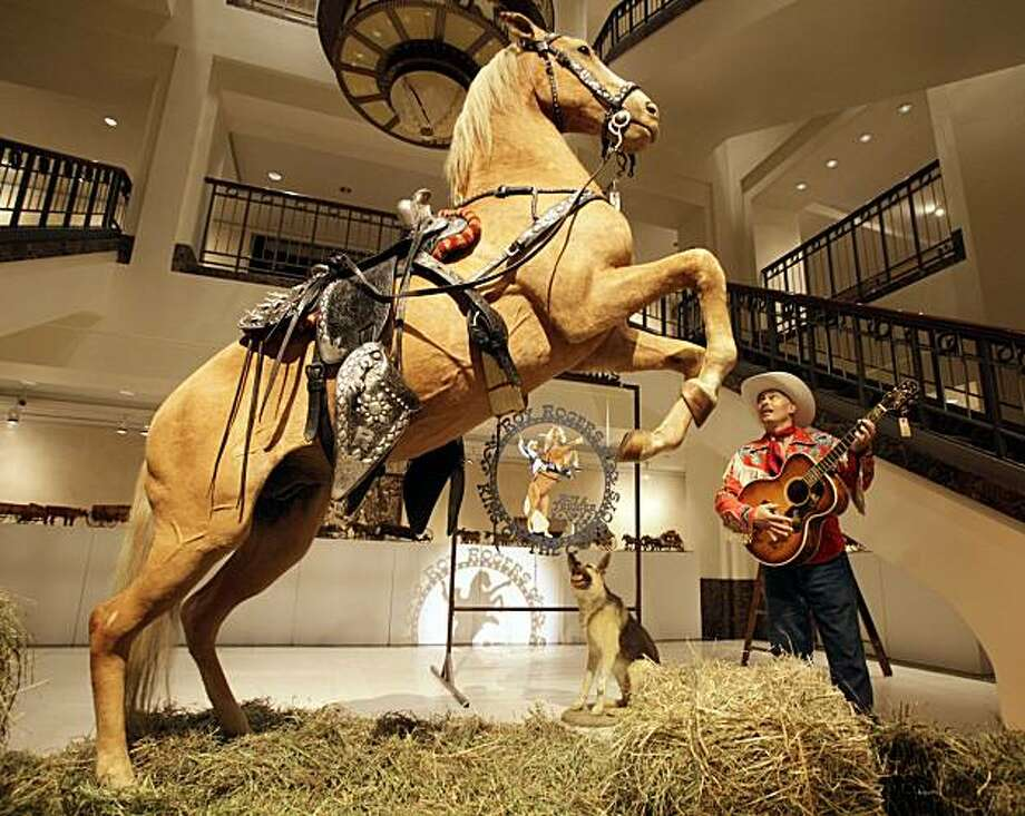 "Gil Perez, right, a doorman at Christies auction house, wears an outfit and holds a guitar belonging  to Roy Rogers as he stands alongside the preserved remains of Rogers' horse ""Trigger"" and dog ""Bullet""  at  the New York auction house,  Friday, July 9,2010.  Christie's held a preview Friday of an upcoming auction of items from the now-closed Roy Rogers and Dale Evans Museum in Branson, Mo. Photo: Richard Drew, AP"