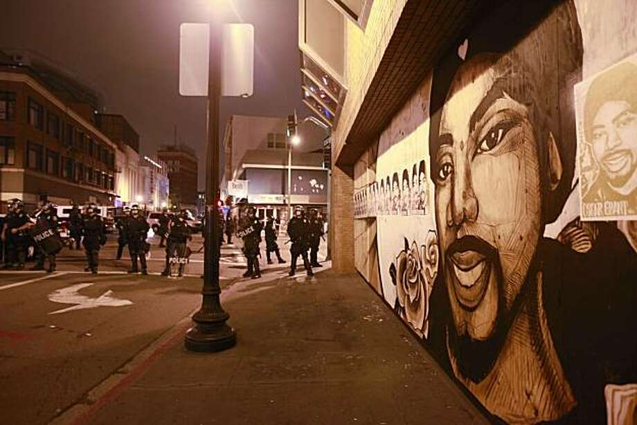 Police line up on a street near a mural of Oscar Grant in Oakland, Calif., after a guilty verdict for Johannes Mehserle, Thursday, July 8, 2010.  Former San Francisco Bay Area Rapid Transit police officer Johannes Mehserle was found guilty of involuntarymanslaughter in Los Angeles for shooting unarmed black man Oscar Grant on New Year's Day 2009 at a BART station in Oakland. Photo: Paul Sakuma, AP