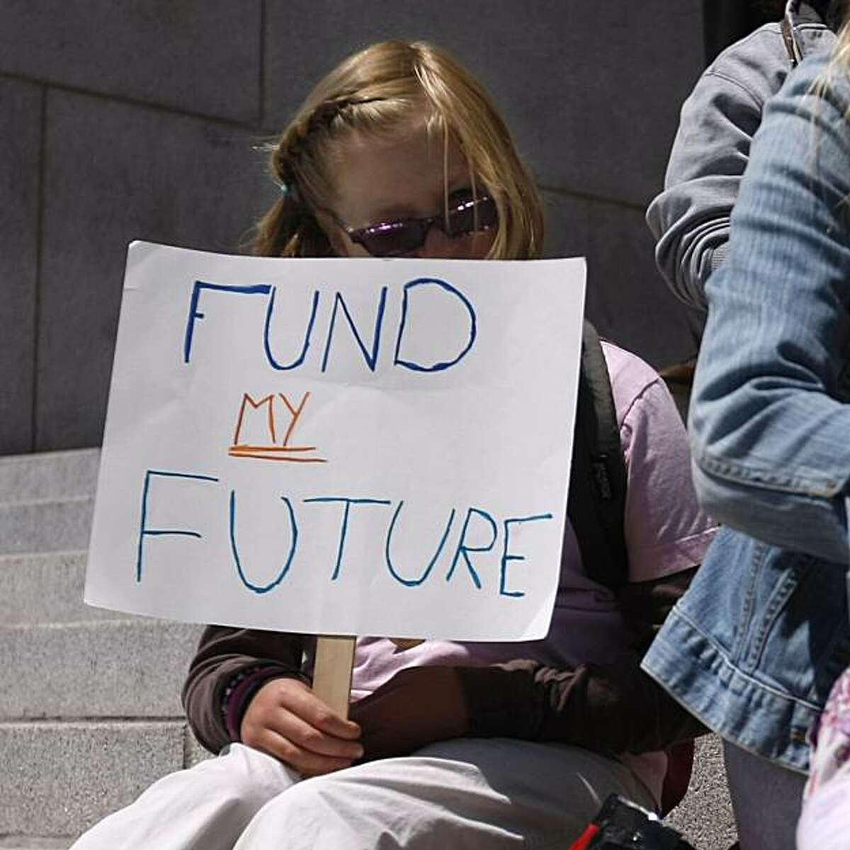 Jessie Moore, 8, of San Francisco, who is going into the fourth grade, sits with others gathered outside the Rene C. Davidson Alameda County Courthouse, Monday July 12, 2010, in Oakland, Calif. The group were there to announce the suit against the state over a school funding system that they say doesn't serve the neediest kids.