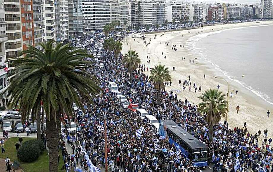 Fans of Uruguay's soccer team surround the players' bus as they arrive to Montevideo after competing in the South Africa 2010 World Cup tournament, Tuesday July 13, 2010. Uruguay placed fourth. Photo: Matilde Campodonico, AP