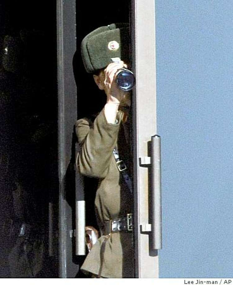 A North Korean soldier uses binoculars to look over the South side at the border village of the Panmunjom (DMZ) that separates the two Koreas since the Korean War, north of Seoul, South Korea, Saturday, Dec. 6, 2008. North Korea said it will no longer treat Japan as a member of the six-party disarmament talks aimed at ending Pyongyang's nuclear programs. (AP Photo/ Lee Jin-man) Photo: Lee Jin-man, AP