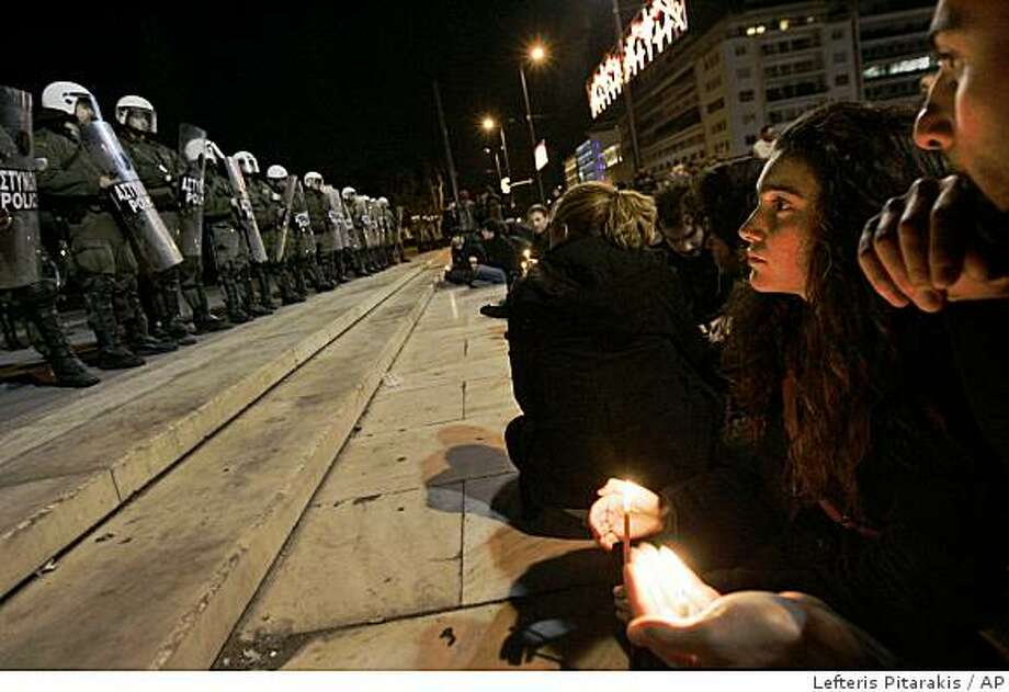 Youths holding candles stage a peaceful protest in central Athens Syntagma Square, late Tuesday, Dec. 9, 2008. Athens and other Greek cities were ravaged by three successive nights or rioting after police shot teenager Alexandros Grigoropoulos dead Saturday night.(AP Photo/Lefteris Pitarakis) Photo: Lefteris Pitarakis, AP