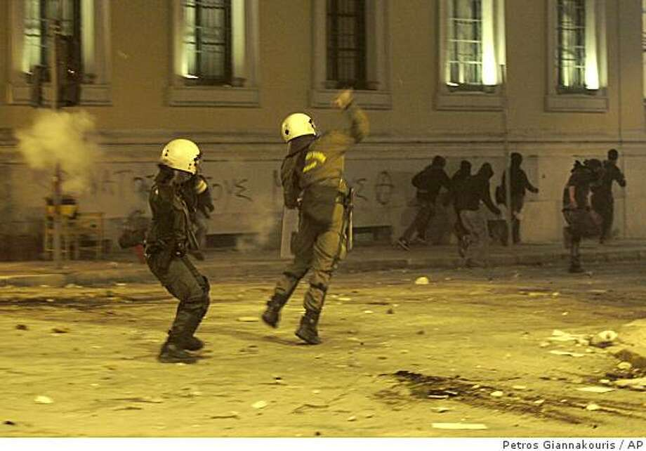 Riot police throw stones as protesters run in the center of Athens as riots went on for a third day in the Greek capital, Monday, Dec. 8, 2008. Gangs of rock-throwing youths made sporadic attacks on police stations across Athens, stoned the Interior Ministry and clashed with riot police outside Parliament on Monday in a third day of violence protesting the police shooting of a teenager. (AP Photo/Petros Giannakouris) Photo: Petros Giannakouris, AP