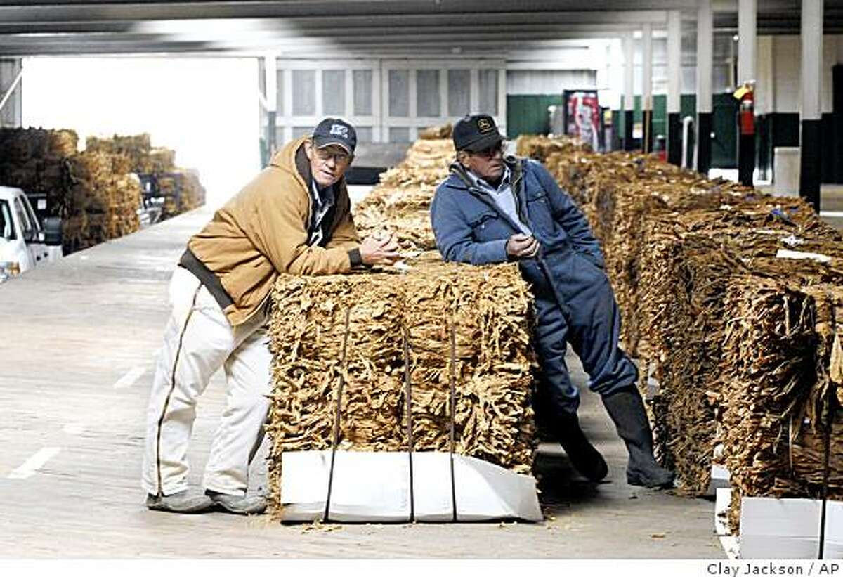 Bennie Pennington, left, and Wayne Art wait to unload tobacco at Farmer's Tobacco Warehouse in Danville, Ky., Monday, Nov. 17, 2008., before auction the following day. A decade ago, tobacco seemed destined to wither as cigarette companies shelled out billions to settle lawsuits and smoking bans swept the country. But as a rebound in production this year shows, Big Tobacco and small growers alike have proven resilient, aided by a boost in exports and by new emphasis on smokeless products. (AP Photo/The Advocate Messenger, Clay Jackson)