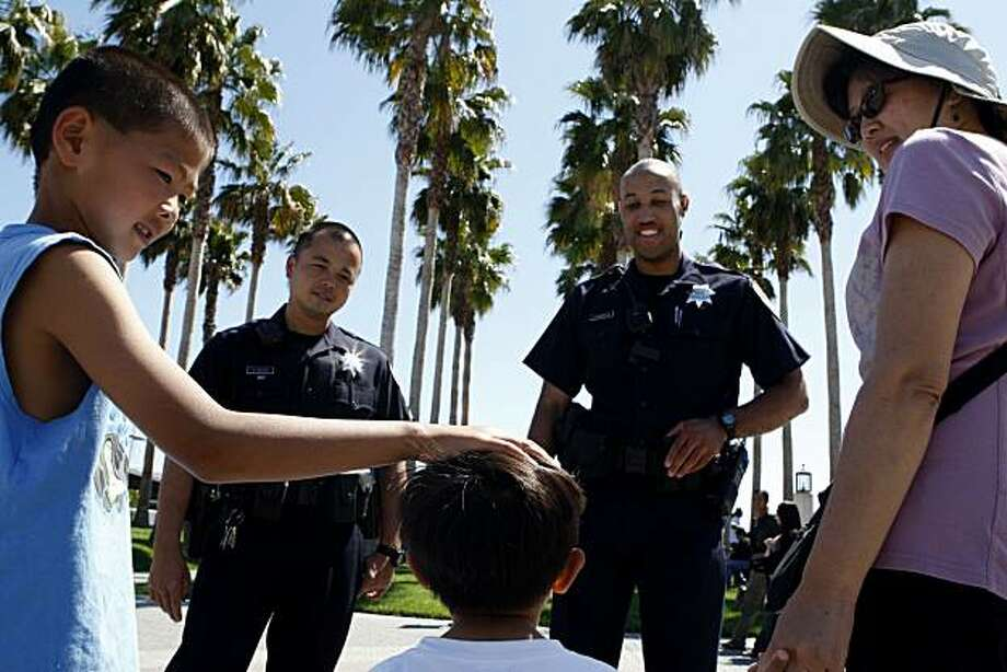 Officer Huy Nguyen (left) and Officer Anthony Banks, Jr. talk with two-year-old Toby Fung (middle), his brother David, 7,  and their mother Serena while on walking patrol of Jack London Square on Sunday, July 11, 2010 in Oakland, Calif. Photo: John Sebastian Russo, The Chronicle