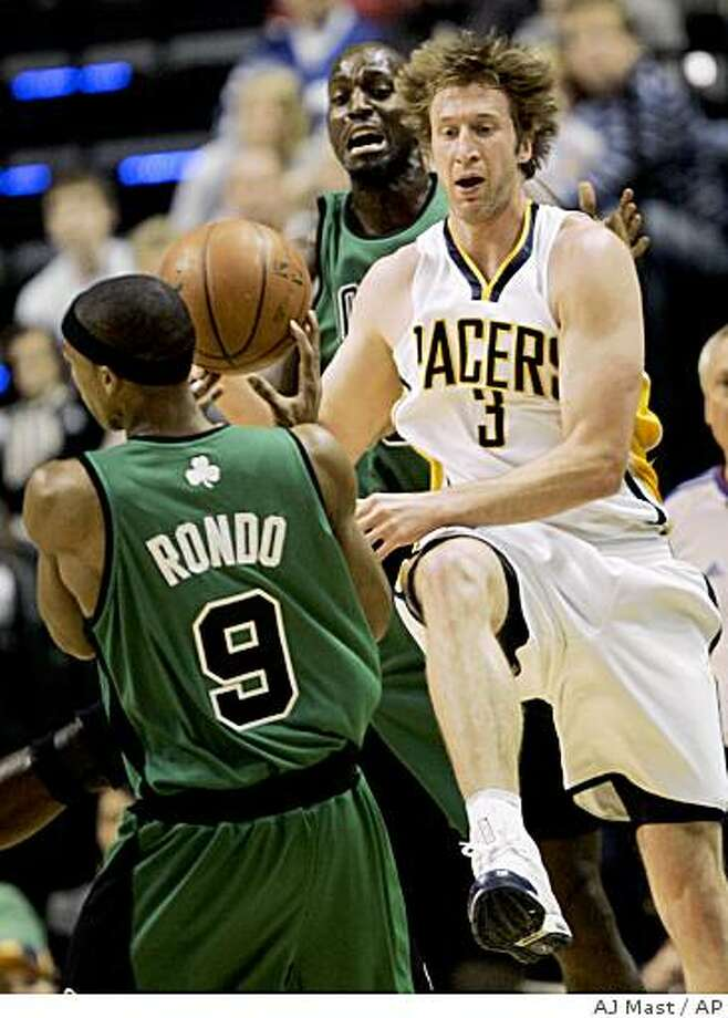 Indiana Pacers forward Troy Murphy (3) throws the ball to Boston Celtics guard Rajon Rondo while trying to save it from going out of bounds in the first half of an NBA basketball game in Indianapolis, Sunday, Dec. 7, 2008.  (AP Photo/AJ Mast) Photo: AJ Mast, AP