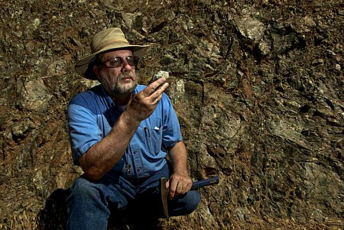 Garry Hayes, Professor of Geology at Modesto Junior College, holds a sample of Serpentine against a solid outcropping of the rock, found along Del Puerto Canyon Road, 20 miles west of Patterson, Ca. on Thursday July 15, 2010. A bill to remove serpentine as California's official state rock was working its way through the state legislature until geologists heard about it and are now taking offense to the proposal. The bill sponsored by a woman whose husband died of asbestos poisoning is supposed to be a symbolic gesture given that serpentine is the source of asbestos.