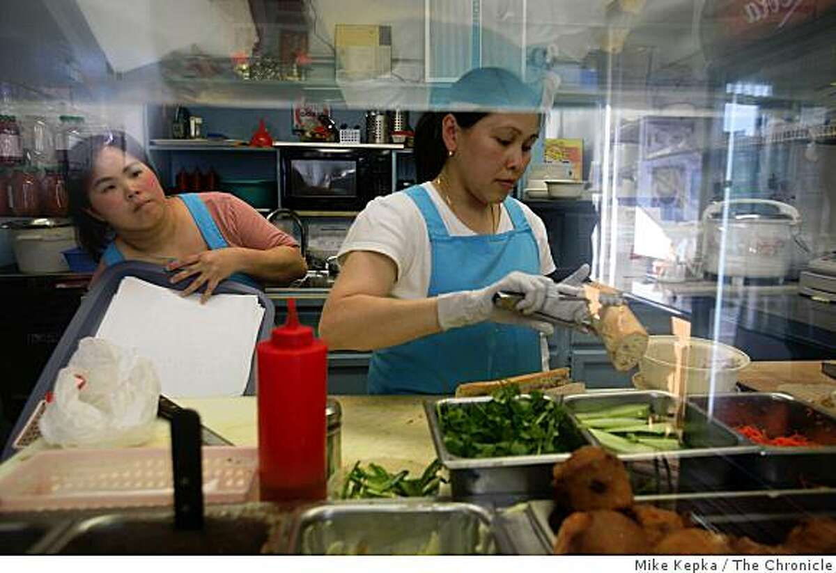 Vivian Tat and Jenny Nguyen make Vietnamese sandwiches at the Irving Cafe and Deli, at on Irving Street near 23rd Avenue, on Friday Dec. 2, 2008 in San Francisco, Calif.