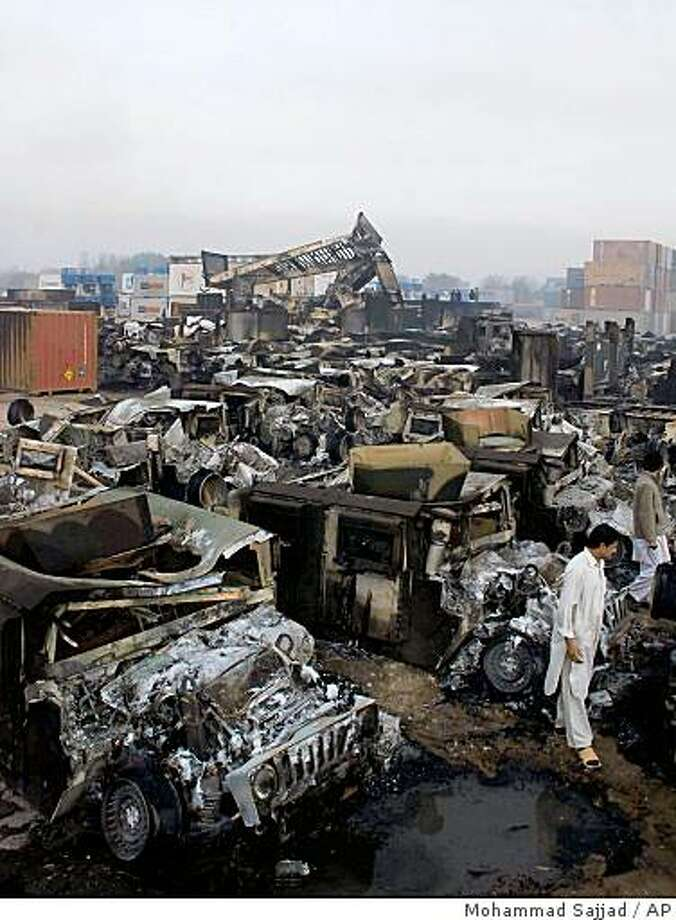 Rows of destroyed Humvees and military trucks are seen at the Portward Logistic Terminal in Peshawar, Pakistan, Sunday, Dec. 7, 2008. Militants blasted their way into two transport terminals in Pakistan on Sunday and torched more than 160 vehicles destined for U.S.-led troops in Afghanistan, in the biggest assault yet on a vital military supply line. (AP Photo/Mohammad Sajjad) Photo: Mohammad Sajjad, AP