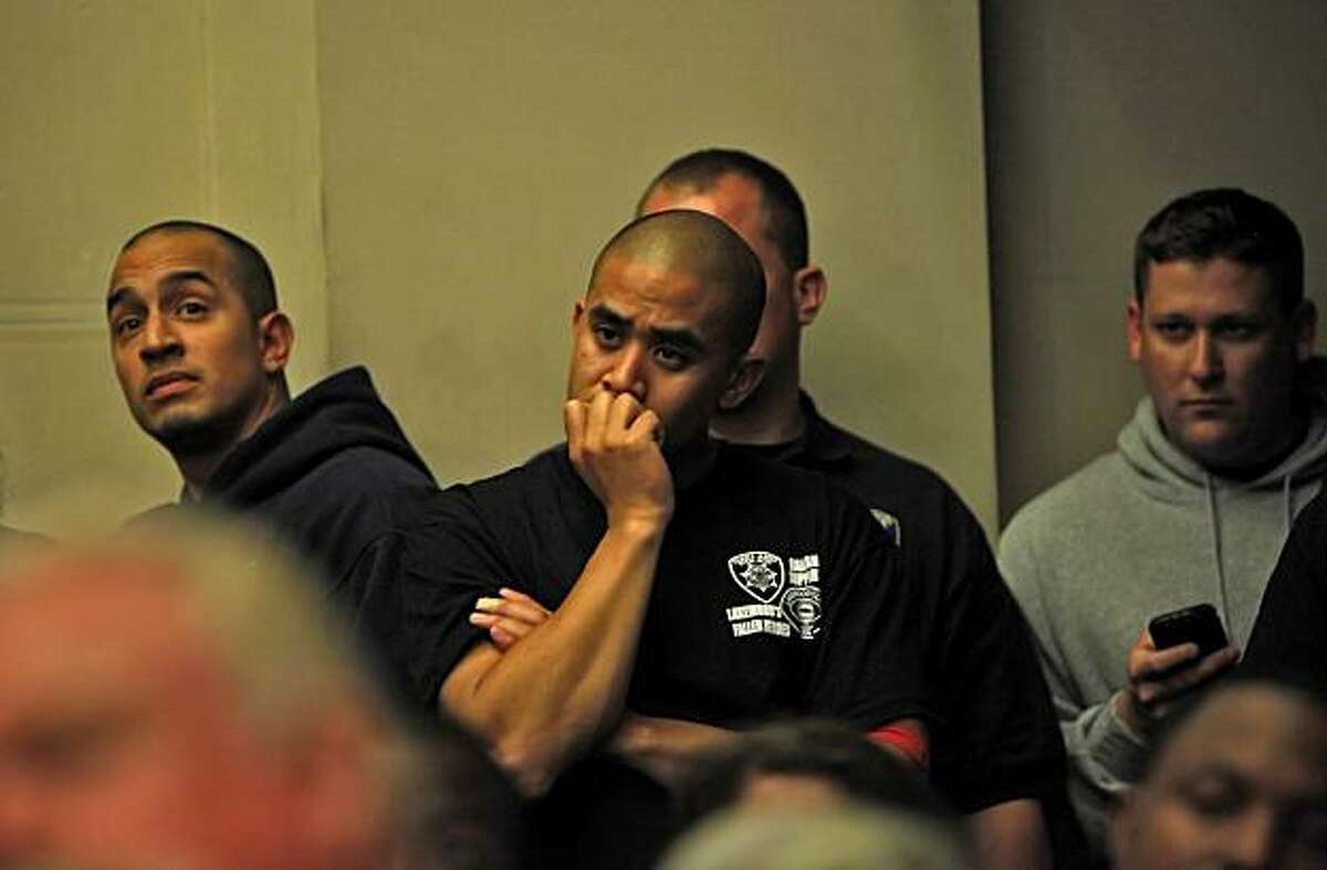 Members of the Oakland Police Department listen as the City Council talks of laying off more than a hundred officers, Thursday June 24, 2010, in Oakland, Calif.