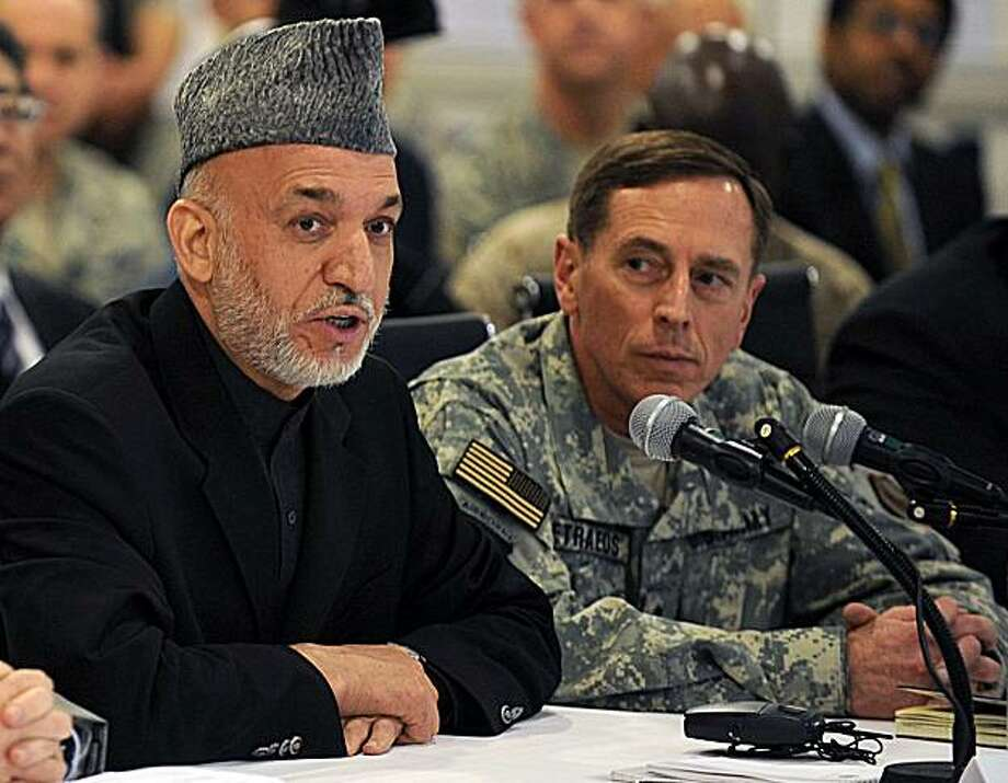 FILE - In this April 11, 2010 file photo, Afghan President Hamid Karzai, left, talks alongside then-U.S. Central Command chief General David Petraeus at Kabul International Airport. Petraeus faces daunting challenges when he assumes command in Afghanistanfollowing what by all accounts will be quick approval by the Senate. Photo: Shah Marai, Associated Press