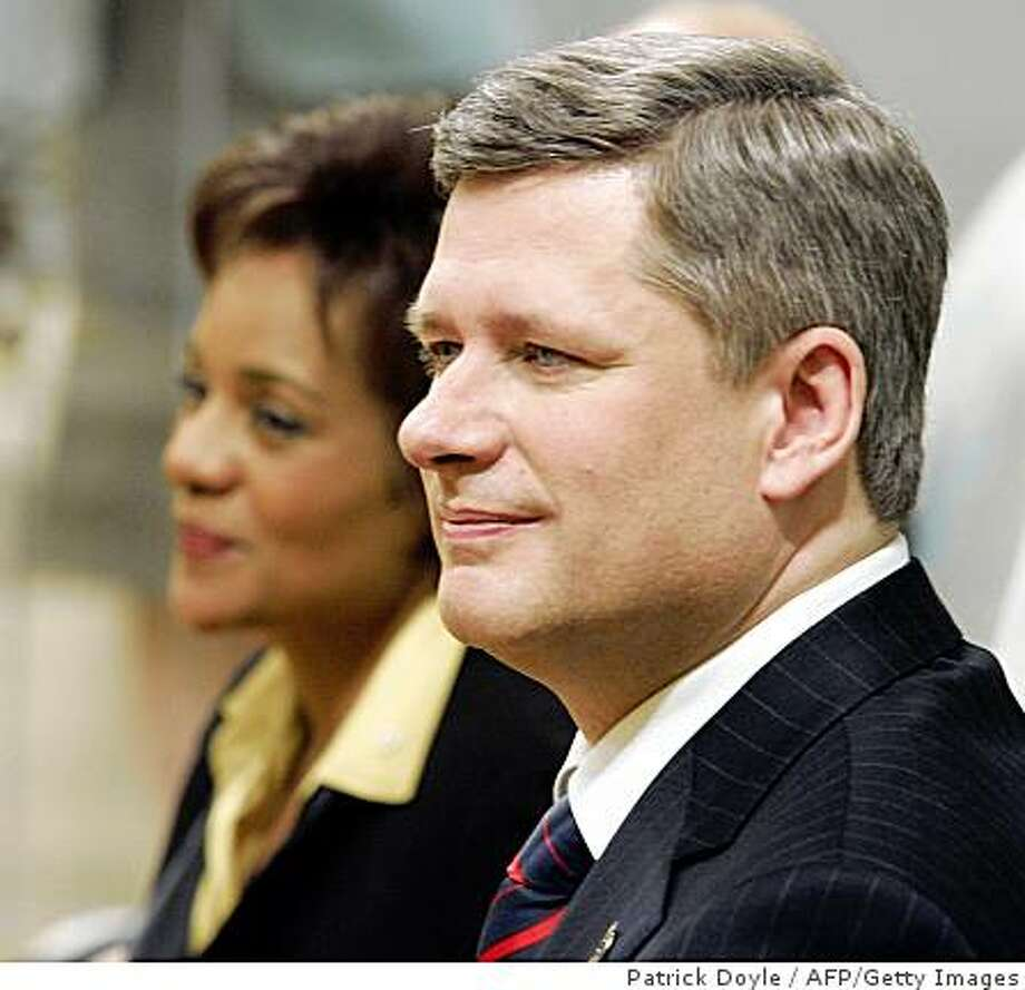 (FILES) Canadian Prime Minister Stephen Harper (R) watches his cabinet ministers being sworn in with Governor General Michaelle Jean (L) during a ceremony 06 February 2006 at Rideau Hall in Ottawa. Harper won a political reprieve on December 4, 2008 by obtaining an unprecedented shutdown of parliament and thwarting an opposition bid to topple his government. After two hours of crisis talks, Jean agreed to Harper's request to suspend the two-week old assembly until the New Year, stymieing the opposition's move to call a no-confidence vote on December 08.    AFP PHOTO/Patrick DOYLE/FILES (Photo credit should read PATRICK DOYLE/AFP/Getty Images) Photo: Patrick Doyle, AFP/Getty Images