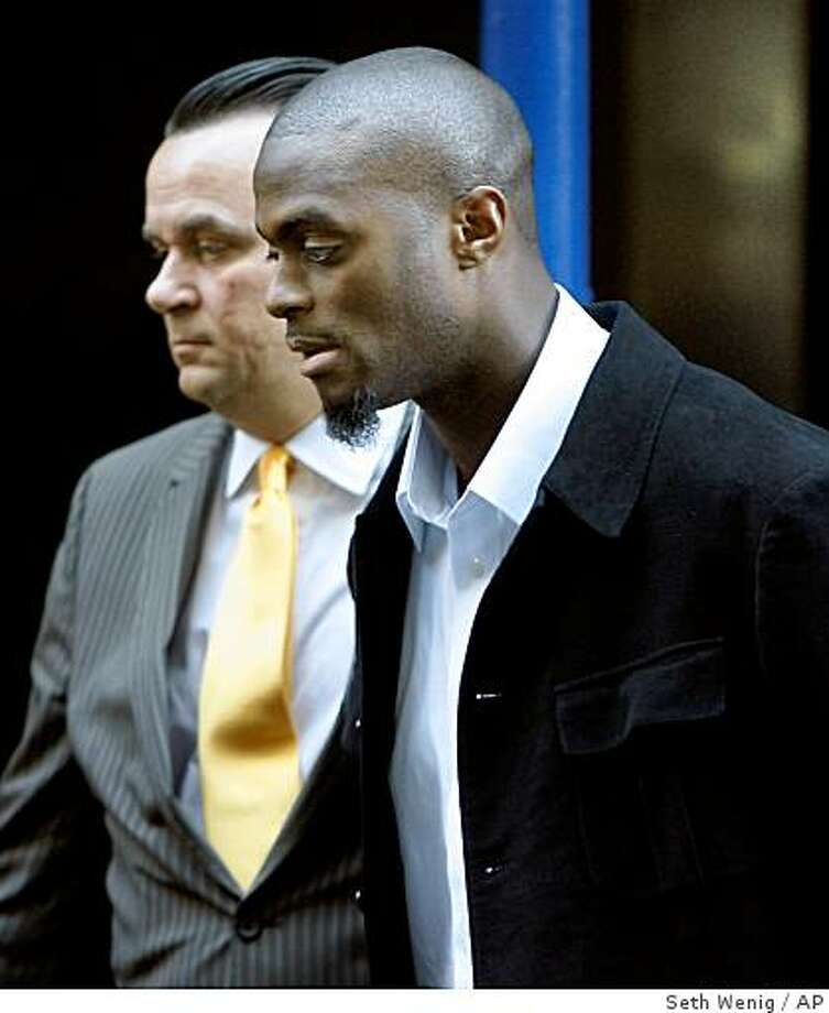 New York Giants wide receiver Plaxico Burress, right, is escorted from a police station in handcuffs, Monday, Dec.1, 2008, in New York. Photo: Seth Wenig, AP