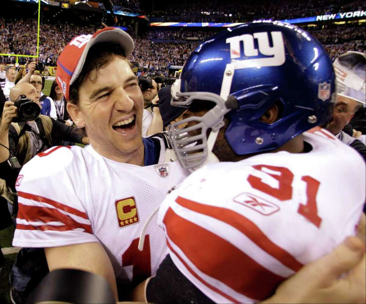 New York Giants quarterback Eli Manning, left, and Justin Tuck celebrate their team's 21-17 win over the New England Patriots in the NFL Super Bowl XLVI football game, Sunday, Feb. 5, 2012, in Indianapolis. (AP Photo/Eric Gay)