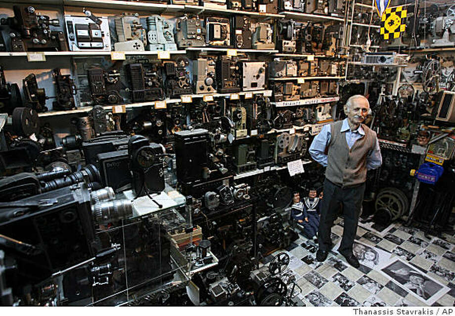 Camera collector Dimitris Pistiolas poses inside his basement museum, with the walls covered in movie cameras and projectors on Friday, Oct. 24, 2008. The museum is the largest of its kind in the world. Pistiolas owns the world's largest private collection of movie cameras _ 937 vintage models and projectors. (AP Photo/Thanassis Stavrakis) Photo: Thanassis Stavrakis, AP