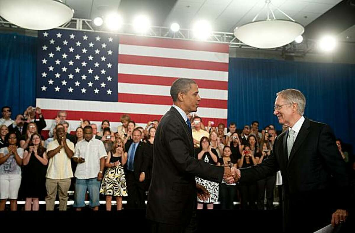 US President Barack Obama shakes hands with Senate Majority Leader Harry Reid before speaking on the economy at the University of Nevada in Las Vegas on July 9, 2010.