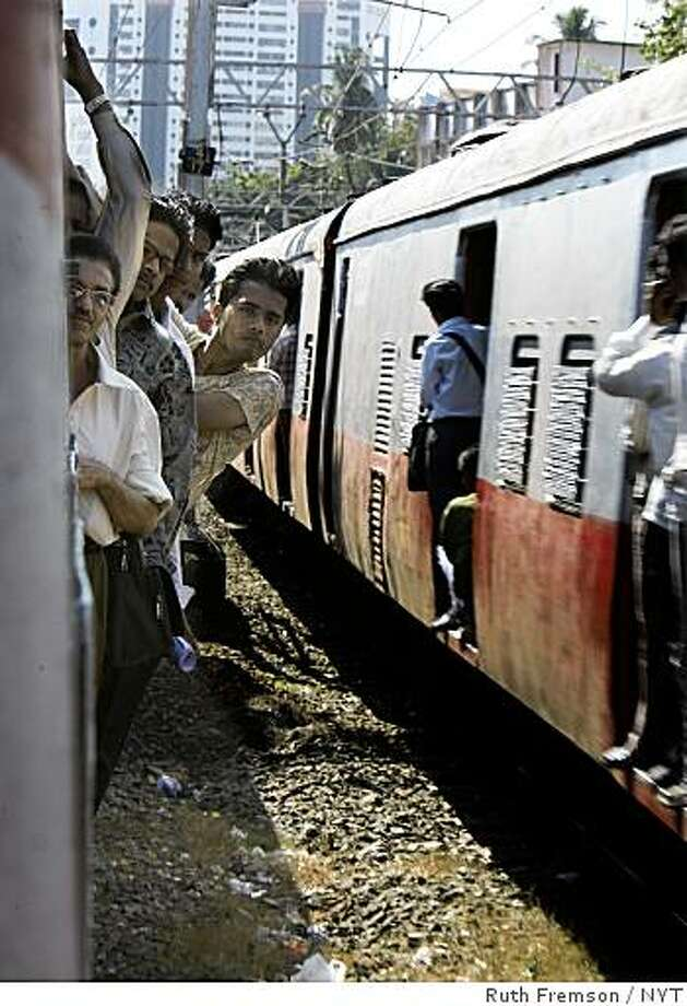 Passengers ride a packed commuter train in Mumbai, India Saturday, December 6, 2008. In India's city of gold, the distinction between public and private can be bewildering. (NYT8) MUMBAI, India -- Dec. 6, 2008 -- INDIA-ATTACKS-REACT-4 -- Passengers ride a packed commuter train in Mumbai, India Saturday, December 6, 2008.  In India's city of gold, the distinction between public and private can be bewildering. (Ruth Fremson/The New York Times) Photo: Ruth Fremson, NYT