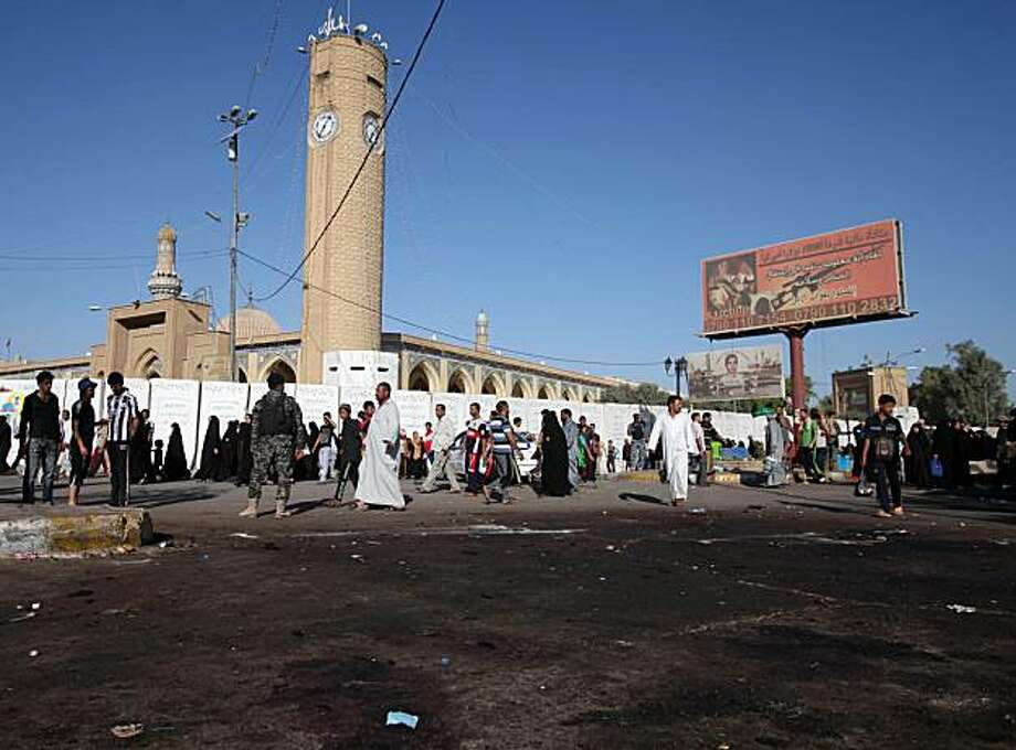 Iraqi security forces are seen at the site of a suicide attack on pilgrims headed to the Imam Moussa al-Kadhim shrine, on the final day of the annual commemoration of the saint's death in Baghdad, Iraq, Thursday, July 8, 2010. Hundreds of thousands of devout Shiites from across the country walk to Baghdad to take part in the occasion. Iraqi officials say a handful of have been killed by bombs targeting pilgrims taking part in the final day of the Shiite religious holiday, a day after scores of pilgrims were killed Wednesday in a suicide attack as they passed through a Sunni neighborhood. Photo: Karim Kadim, AP