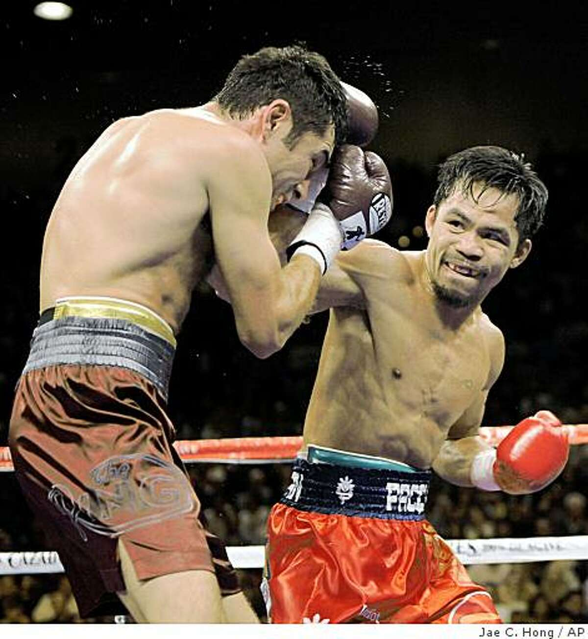 WBC lightweight champion Manny Pacquiao, right, throws a right to the head of Oscar De La Hoya during the fourth round of their welterweight boxing match in Las Vegas, Saturday, Dec. 6, 2008. (AP Photo/Jae C. Hong)