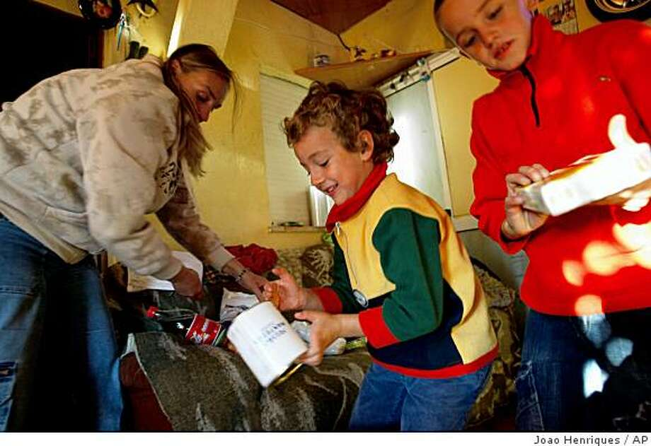 **APN ADVANCE FOR SUNDAY DEC. 7** Maria de Assuncao Cunha, left, and her sons Ricardo Bernardo, 8, right, and Rodrigo, 5, stow food aid items at their her home in Belas, outside of Lisbon, Portugal on Thursday, Nov. 13, 2008. Cunha, mother of three, is unemployed and on welfare.  Cunha and her husband who works in construction rely on food aid to help feed their family. The European Union, a major global aid donor, is currently considering a steep increase in annual food aid to its own citizens. Officials estimate 43 million people in the 27-nation bloc cannot afford a balanced nutritional meal every two days.(AP Photo/Joao Henriques) Photo: Joao Henriques, AP