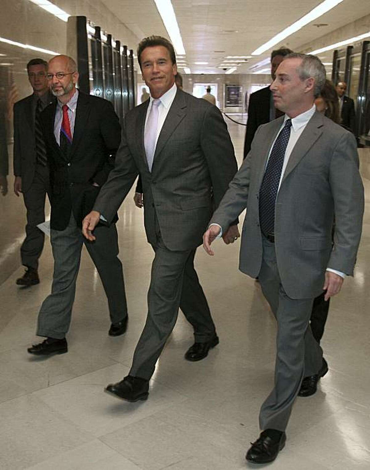 Gov. Arnold Schwarzenegger, center, walks to a Capitol news conference where he discussed a proposed redistricting plan, in Sacramento, Calif., Tuesday, Dec. 5, 2006. He is flanked by former state Assemblyman Fred Keeley, D-Santa Cruz, left, and Dan Schnur, former adviser to Gov. Pete Wilson. (AP Photo/Rich Pedroncelli)