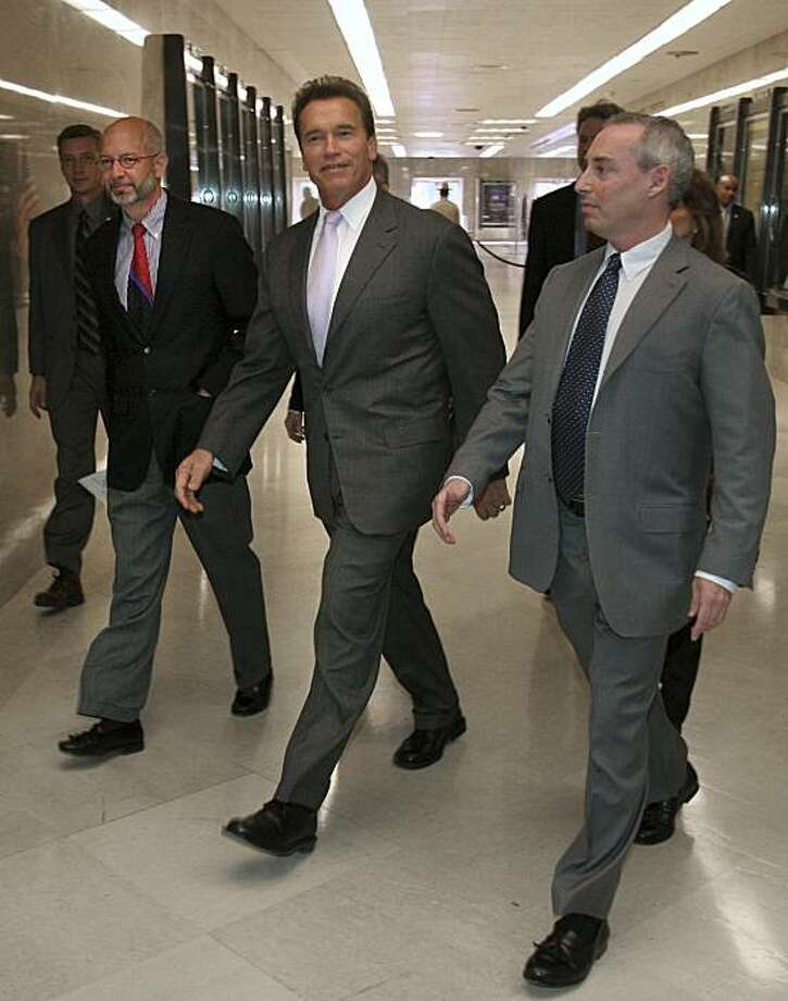Gov. Arnold Schwarzenegger, center, walks to a Capitol news conference where he discussed a proposed redistricting plan, in Sacramento, Calif.,  Tuesday, Dec. 5, 2006.  He is flanked by former state Assemblyman Fred Keeley, D-Santa Cruz, left, and Dan Schnur, former adviser to Gov. Pete Wilson.   (AP Photo/Rich Pedroncelli) Photo: Rich Pedroncelli, AP